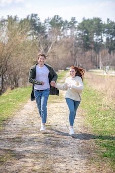 良い瞬間。晴れた春の日に自然の中で余暇を積極的に過ごして走っているセーターとジーンズでエネルギッシュな男女の笑顔