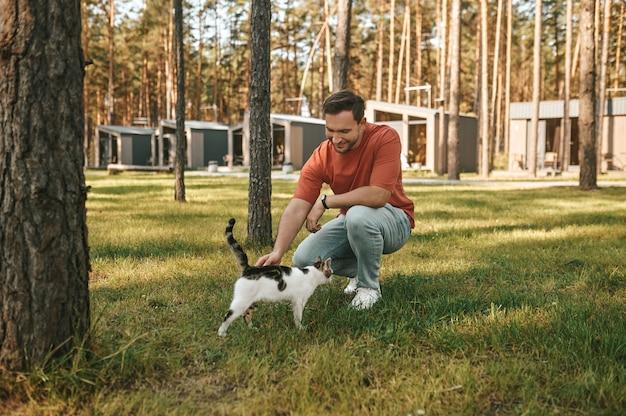 良い瞬間。晴れた日にレクリエーションエリアで屋外の猫に触れる芝生の上にしゃがみ込んだtシャツとジーンズで若い男を笑顔