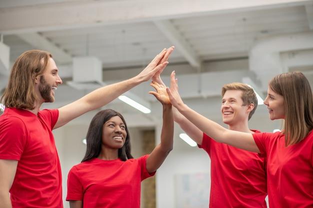 좋은 순간들. 열정적 인 분위기로 실내에 서있는 제기 손의 손바닥을 만지는 동일한 티셔츠에 두 어린 소녀와 남자