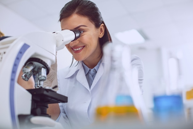 Good mood. alert professional biologist wearing a uniform and looking into the microscope