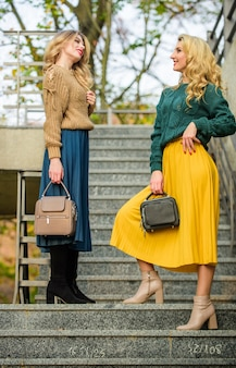 Хорошее настроение в любую погоду. подружки идут наверх. цветовые тенденции осеннего сезона. плиссированный тренд. девушки в гофрированной юбке и свитере. женская красота. мода на трикотаж. стильные осенние женщины на открытом воздухе.