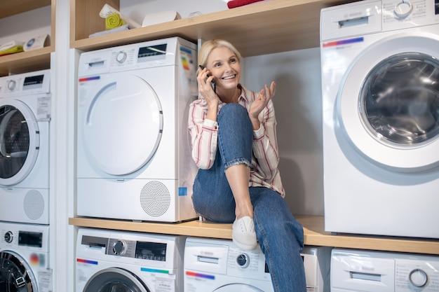 좋은 분위기. 세탁기에 앉아 웃고 스트라이프 셔츠에 금발의 여자