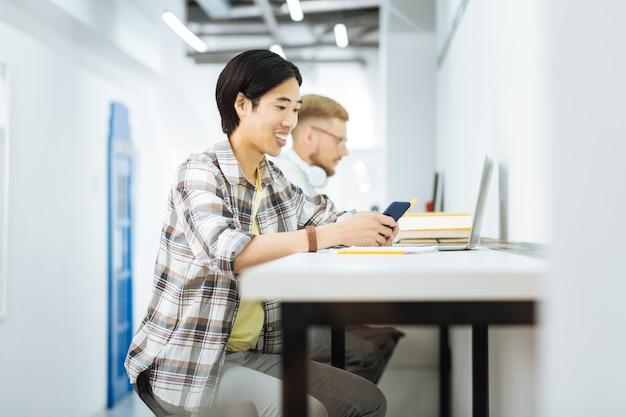 Хорошее настроение. веселый азиатский человек улыбается и смотрит на экран современного смартфона, сидя за столом и читая сообщения от друзей
