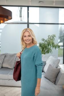 좋은 분위기. 실내 서 그녀의 어깨에 와인 색 가방 그녀의 손목에 팔찌와 쾌활 한 여자.