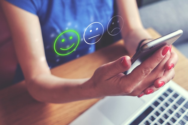 Good mood concept made of emoticon and rating. the girl puts an assessment using a smartphone.