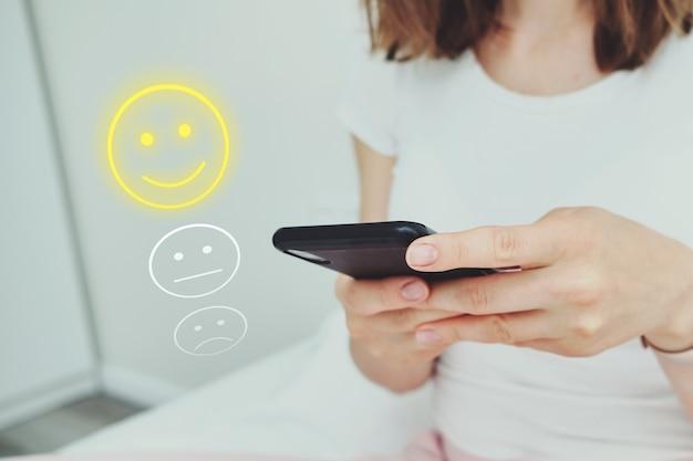 이모티콘과 평가로 만든 기분 좋은 컨셉. 소녀는 전화를 통해 인터넷을 사용합니다.
