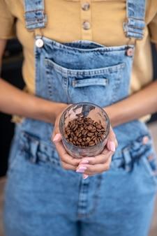 良い雰囲気。女性の細い手に高品質のコーヒー豆のガラス、顔は見えません