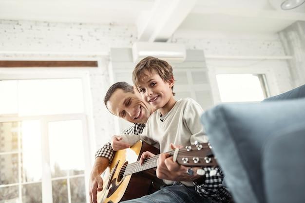 良い雰囲気。ソファに座ってギターを弾くことを学ぶハンサムな笑顔の金髪の少年と彼の父親の笑顔