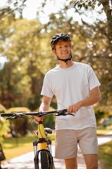 Хорошее настроение. счастливый улыбающийся рыжеволосый парень в черном шлеме с велосипедом на прогулке в парке в теплый солнечный день