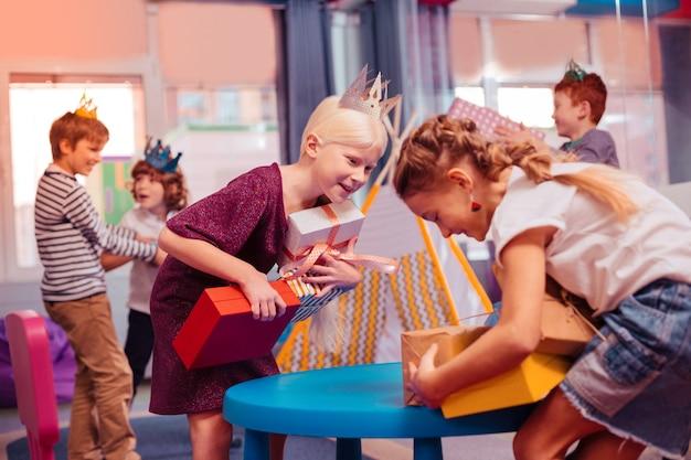 좋은 분위기. 다채로운 상자를 들고 얼굴에 미소를 유지하는 즐거운 작은 여성