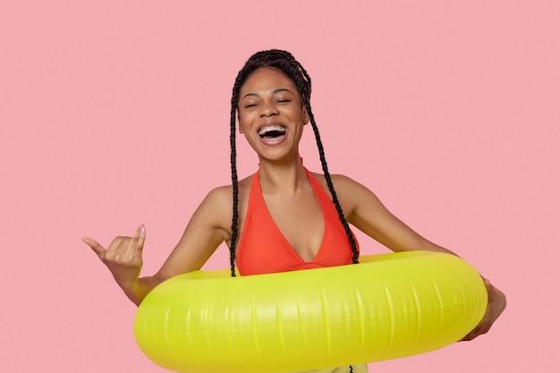 좋은 분위기. 노란색 튜브를 들고 즐겁게 웃고 있는 아프리카계 미국인 여성