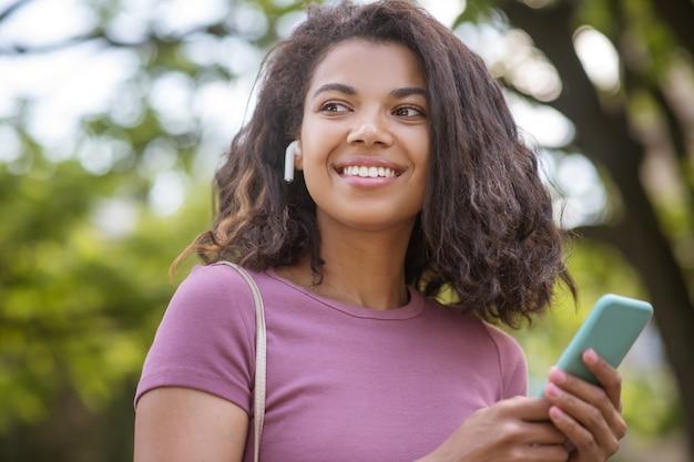 Хорошее настроение. улыбающаяся темнокожая девушка выглядит счастливой и довольной Premium Фотографии