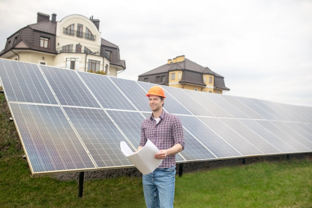 Good mood. smiling young adult man in safety helmet with drawing on background of large solar panel standing on green grass