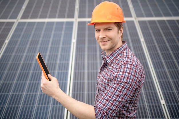 Хорошее настроение. улыбающийся молодой привлекательный мужчина в защитном шлеме и клетчатой рубашке с планшетом во время работы на специальном объекте на открытом воздухе