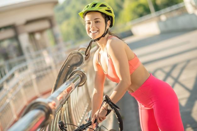 良い雰囲気。幸せで満足しているように見える明るいスポーツウェアの若いサイクリスト
