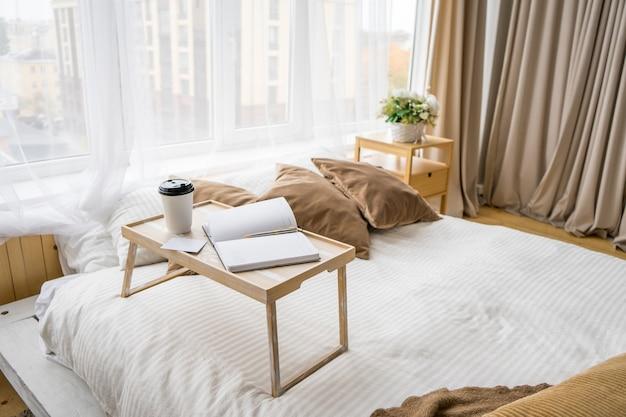 Доброе утро. чашка кофе в постели. закройте вверх. в бежевом салоне. макет карты. фото высокого качества