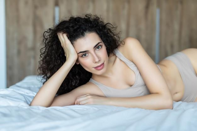 좋은 아침. 미소하고 집에서 침대에 누워있는 동안 찾고 매력적인 젊은 여자