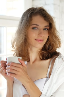 おはようございます!朝、窓際に座ってコーヒーを飲みながら白いランジェリーを着た美しい女性。