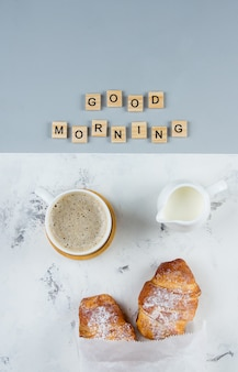 Good morning breakfast minimal concept. cup of coffee, croissant and text good morning, flat lay
