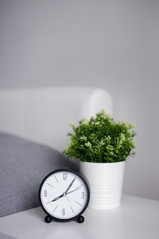 Good morning concept - alarm clock on bedside table and copy space over gray wall