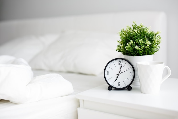 Good morning concept - alarm clock and cup of coffee on bedside table and unmade bed at home or hotel