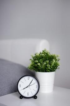 おはようのコンセプト-ベッドサイドテーブルの目覚まし時計と灰色の壁の上のコピースペース