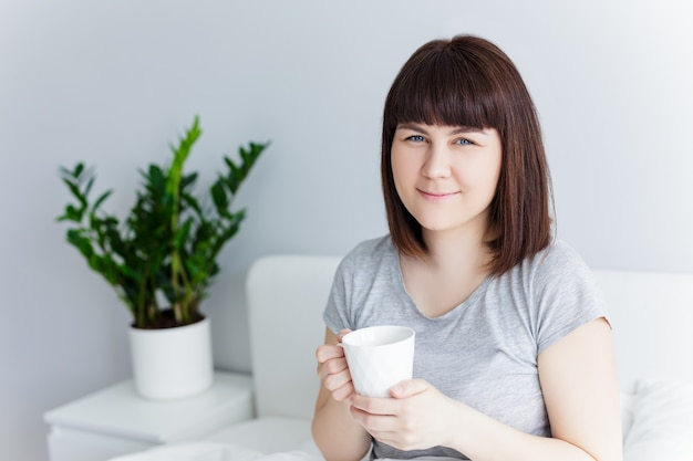 Good morning concept - portrait of happy woman drinking coffee at home