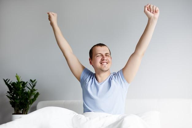 おはようコンセプト-寝た後にベッドでストレッチ若いハンサムな男の肖像画
