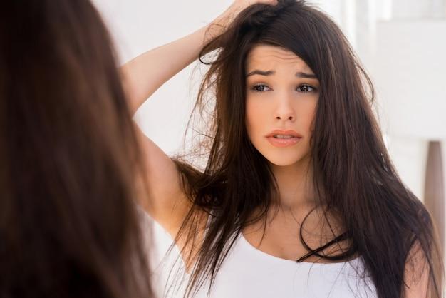 좋은 아침? 좌절한 젊은 여성이 거울에 비친 자신의 모습을 보고 머리를 잡고 손을 잡고 있다