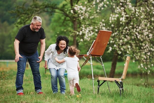 Доброе утро. бабушка и дедушка веселятся на природе с внучкой. концепция живописи