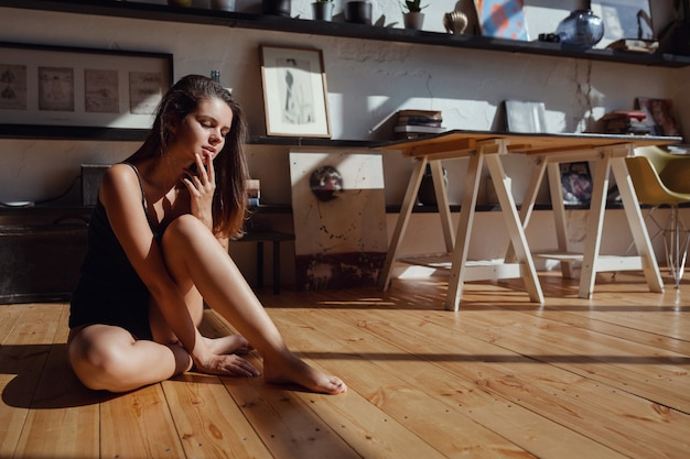 Good morning, happy and joyful morning. sun is shining into the bedroom, woman looks out the window sitting on the wooden floor