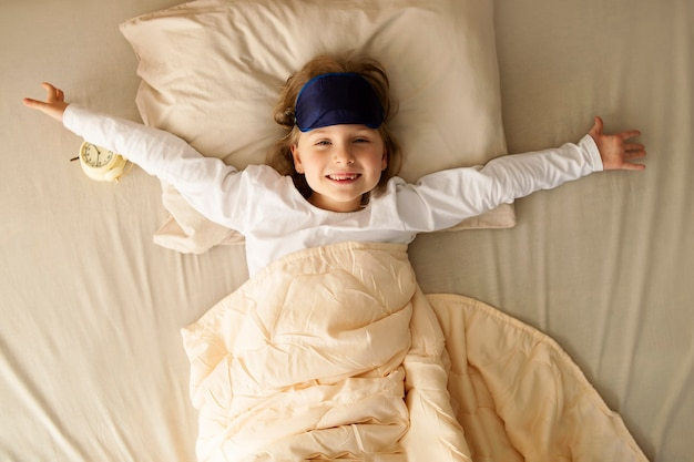 Good morning hello a preschool girl woke up and stretches in bed stretches out his arms in different directions and smiles good healthy sleep slept well