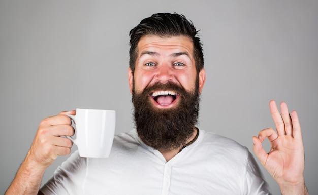 Доброе утро, мужик, чаю, хорошо. улыбающийся хипстерский мужчина с чашкой свежего кофе