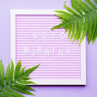Good morning phrase on letter board with with green fern leaves