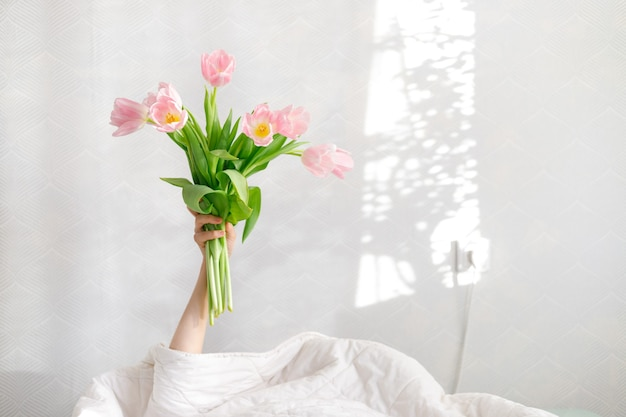 Good morning pink tulips in a woman's hand in bed, birthday greetings, international women's day, valentine's day, gift, flowers, pink bouquet, spring tulips, surprise