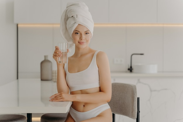 Good morning. portrait of young slim female model posing with glass of water and smiling at camera, sitting in kitchen in white classic underwear and bath towel wrapped on head. healthcare concept