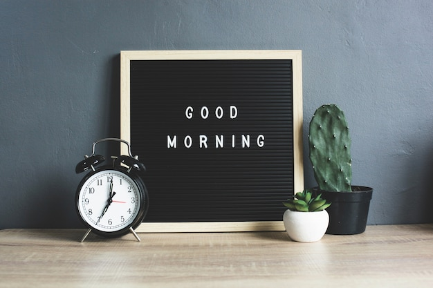 Good morning quote on blackboard with classic alarm clock, cactus and succulent on wooden table