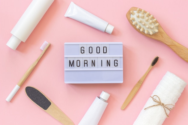 Good morning and set of cosmetics products and tools for shower or bath on pink background