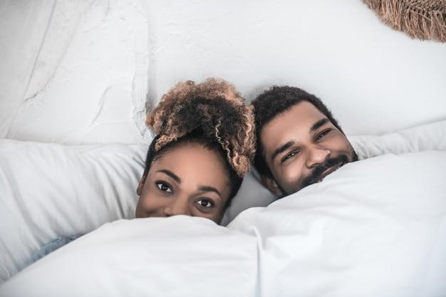 Доброе утро. улыбающиеся темнокожие счастливые мужчина и женщина, лежащие под белым одеялом, видны только лица