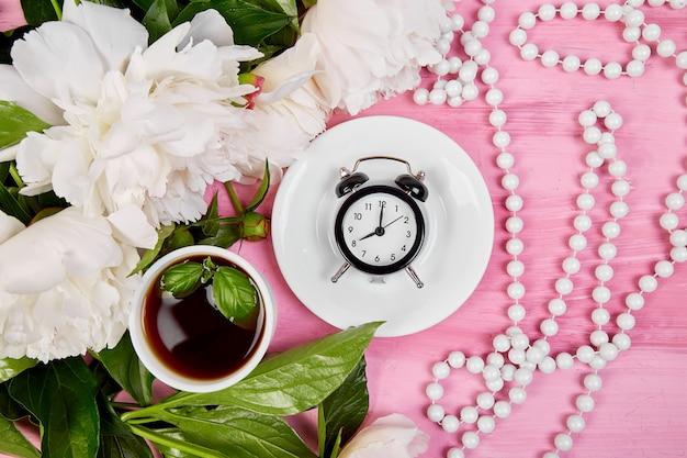 Good morning.  tea, alarm clock and peony