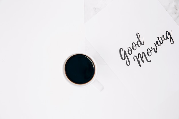 Good morning text on paper with coffee cup against white background