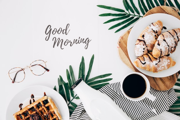 Good morning text with eyeglasses; fresh baked croissant; waffles; bottle and coffee cup on white desk