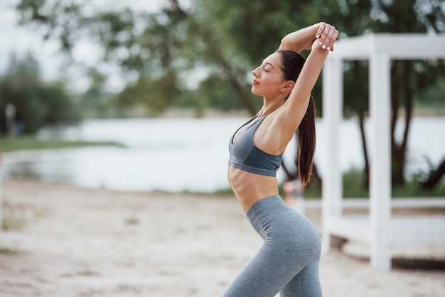 Доброе утро. брюнетка с красивой формой тела в спортивной одежде занимается фитнесом на пляже