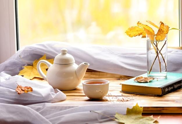 おはようございます。太陽と焦点がぼけた自然の背景と窓にお茶と伝統的な中国のティーポットとボウル。自宅での心地よさのコンセプト。