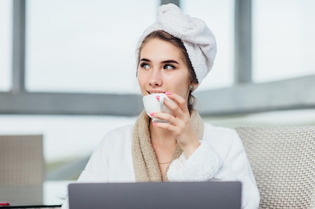 Good morning with cup of coffee. pretty girl with her laptop in white robe sits on terrace.