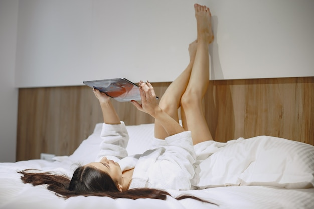 Good morning. woman in a bed. lady in the bedroom. brunette with tablet.