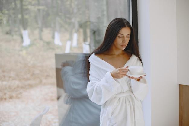 おはようございます。女性はコーヒーを飲みます。窓際の女性。