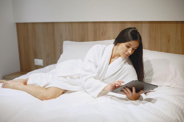 좋은 아침. 침대에있는 여자. 침실에있는 아가씨. 태블릿 갈색 머리.