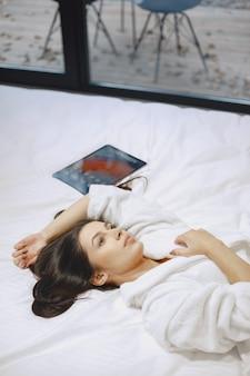 Доброе утро. женщина в постели. дама в спальне. брюнетка с планшетом.