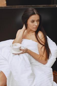 おはようございます。毛布の中の女性。テラスに座っている女性。ブルネットはコーヒーを飲みます。
